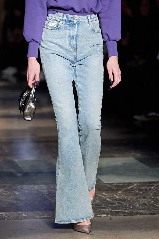 Девушка в светло голубых джинсах клеш, фиолетовый свитер и маленькая сумочка дополняют образ