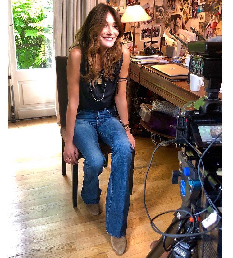 Карла Бруни в синих джинсах клеш и черном топе