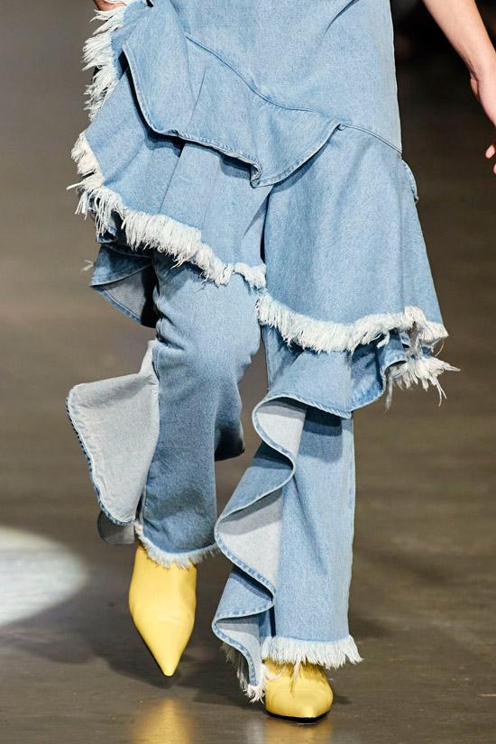 Модель в голубых джинсах-юбке с рюшами и бахромой, желтые ботильоны