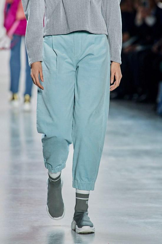 Модель в голубых спортивных джинсах, серые кеды и толстовка