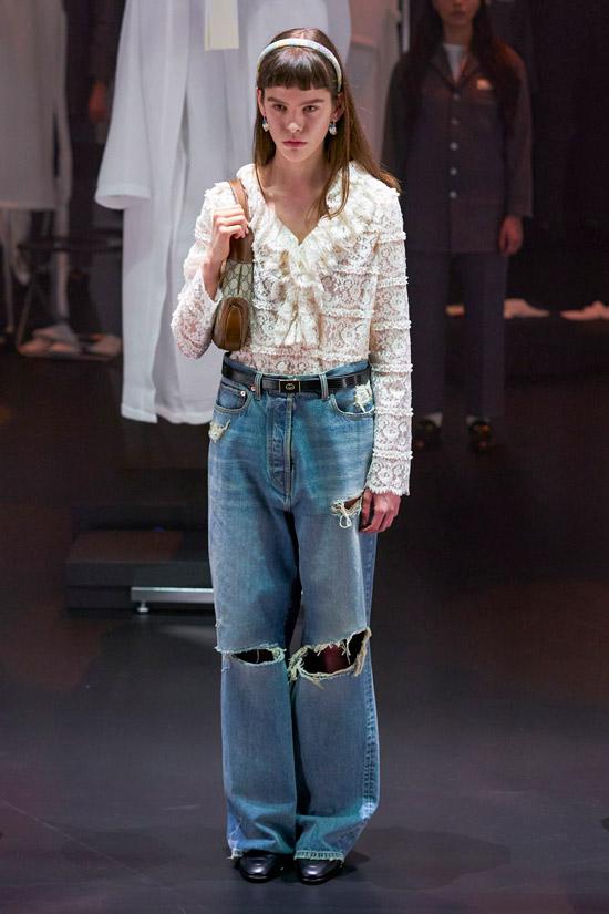 Модель в широких голубых джинсах с большими дырками на коленях, образ допоняет нежная белая блузка с кружевами