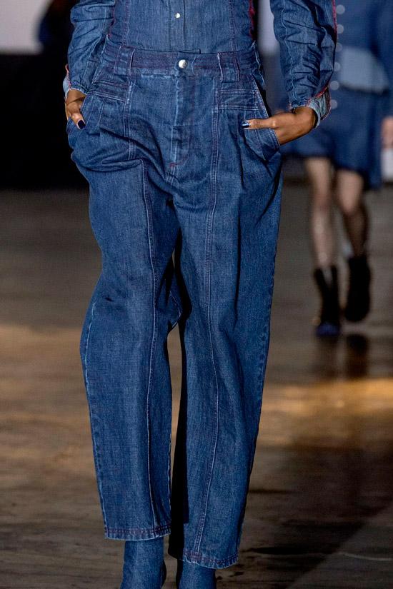 Модель в синих свободных джинсах и джинсовой рубашке темного цвета
