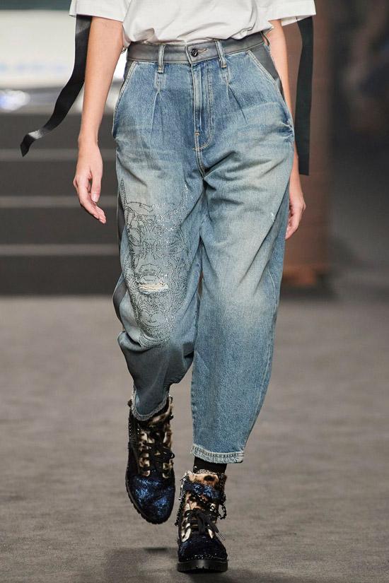Модель в свободных укороченных джинсах, простая футболка и ботинки на шнуровке