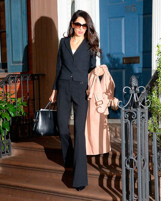 Амаль Клуни в черных брюках клеш, укороченный пиджак и большая сумка