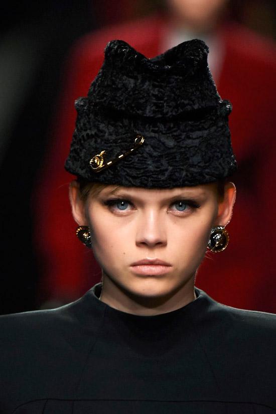 Модель в черной шапке с золотой булавкой от Versace