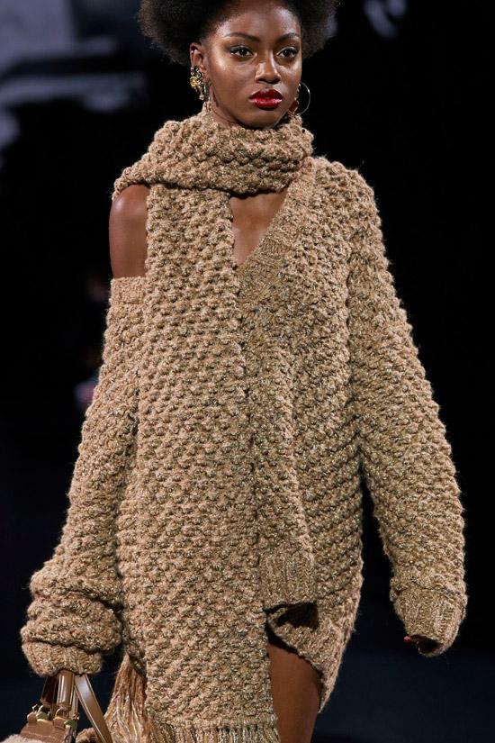 Модель в коричневом вязанном платье мини с шарфом