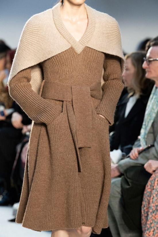 Модель в коричневом вязаном платье с поясом и накидка на плечи