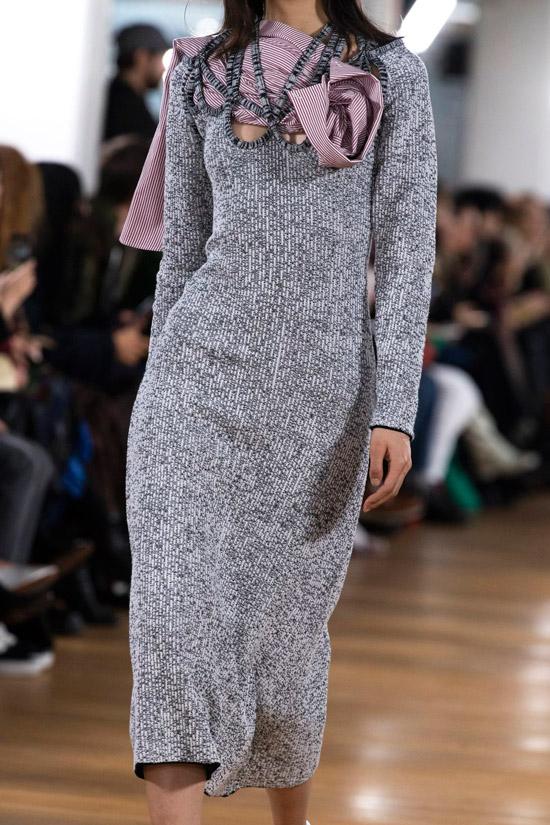 Модель в простом сером платье с длинными рукавами