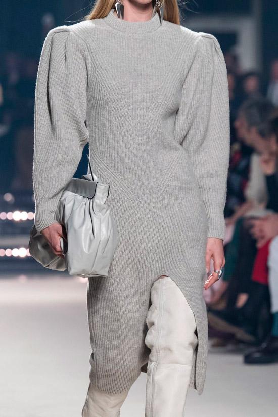 Модель в сером вязаном платье с объемными рукавами и белые сапоги выше колен
