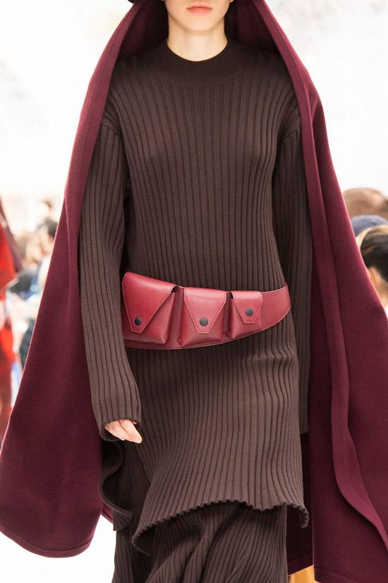 Модель в темном вязаном платье с красным поясом и бордовое пальто