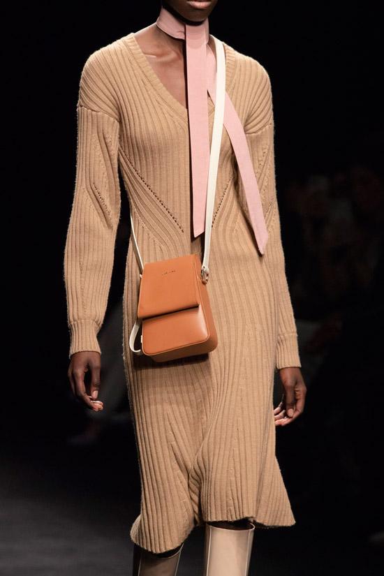 Модель в вязаном бежевом платье миди, высокие сапоги и сумочка