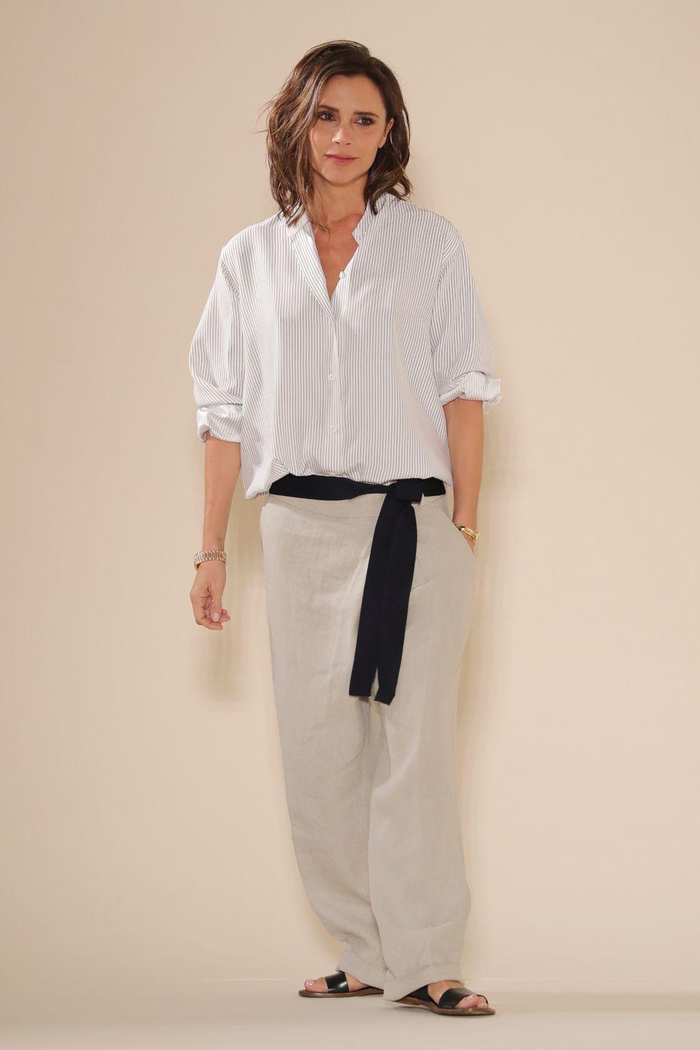 Виктория Бекхэм в бежевых широких брюках, белая свободная рубашка и черный пояс