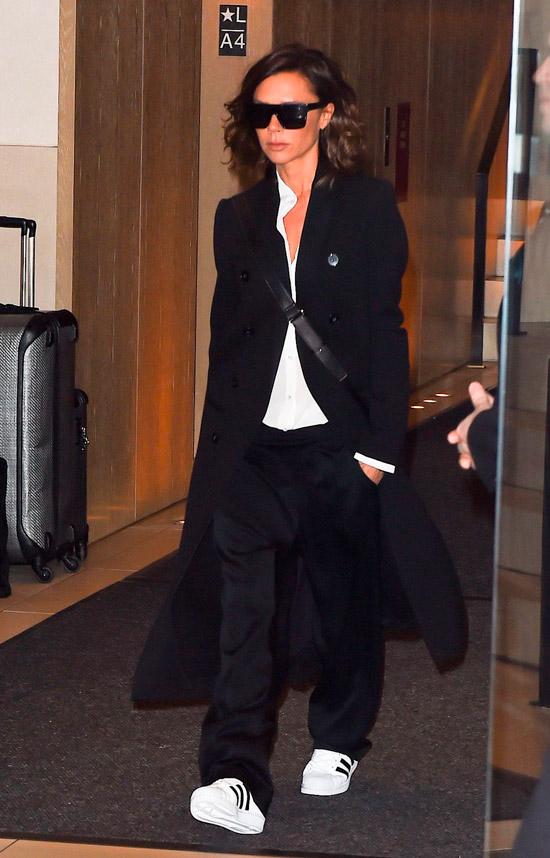 Виктория Бекхэм в черных брюках, белая рубашка и черное пальто