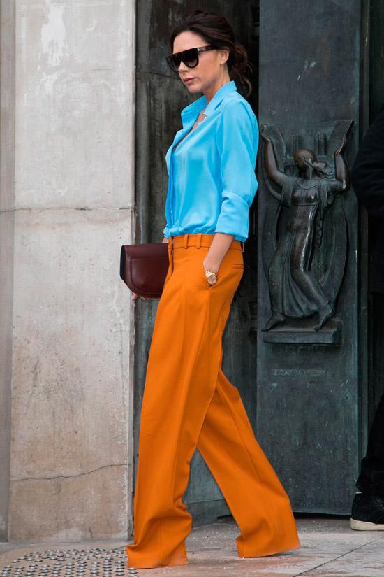 Виктория Бекхэм в оранжевых широких брюках, голубая рубашка и клатч