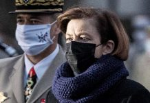 57-летняя французская министр в пальто, брюках и сапогах выглядит просто и элегантно