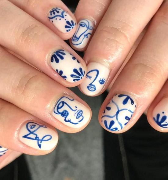 Белый с синими узорами маникюр в стиле Пикассо