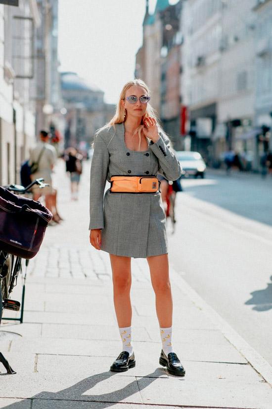 Девушка в сером мини платье с поясной сумкой и лакированные черные лоферы