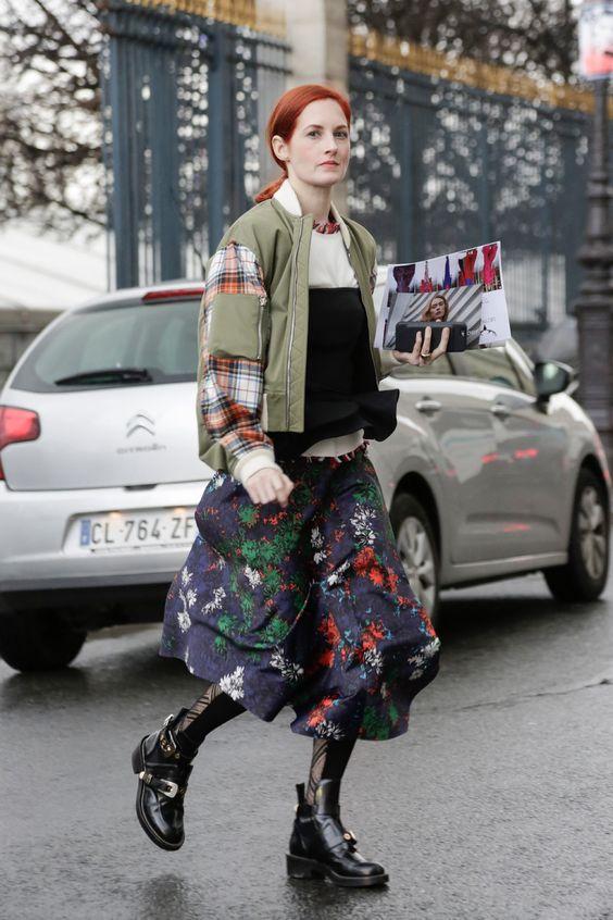 Девушка в черной юбке миди с цветочным принтом и военная куртка, образ дополняют черные ботинки