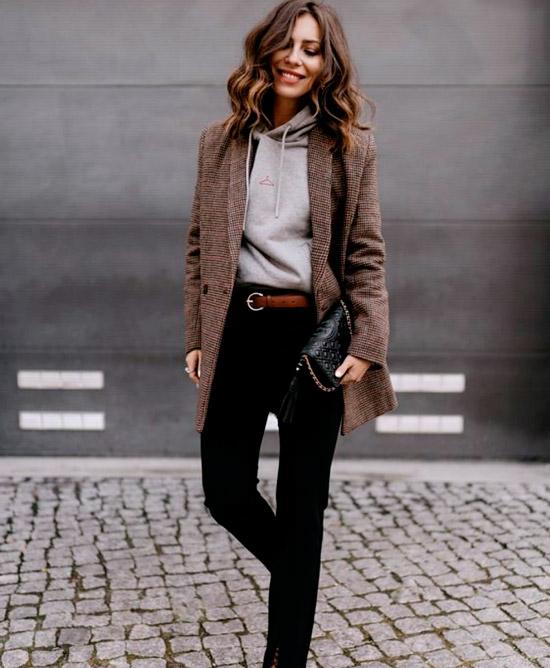 Девушка в черных джинсах с ремнем, серая толстовка и коричневый удлиненный пиджак