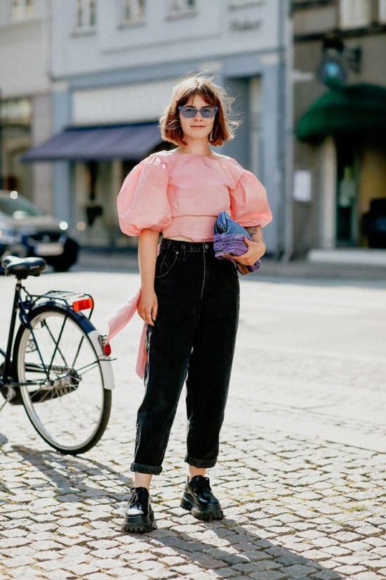 Девушка в черных свободных джинсах, розовая блузка с пышными рукавами и лоферы на объемной платформе