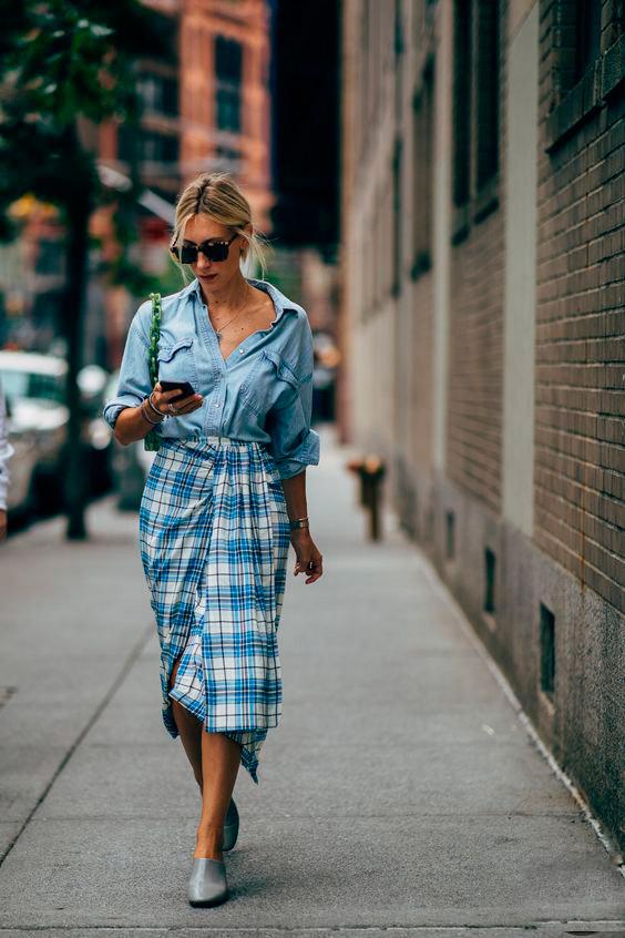 Девушка в голубой юбке в клетку с джинсовой простой рубашкой, образ дополняют солнцезащитные очки и светлые туфли