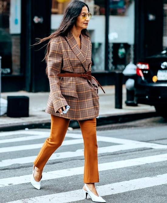 Девушка в коричневых брюках, блейзер оверсайз с ремнем на талии, образ дополняют белые туфли на низком каблуке
