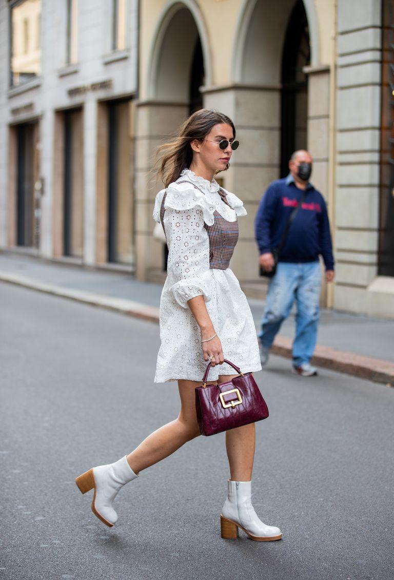 Девушка в коротком платье белого цвета с воротничком и рукавами, образ дополняют белые ботильоны на устойчивом каблуке и бордовая сумочка
