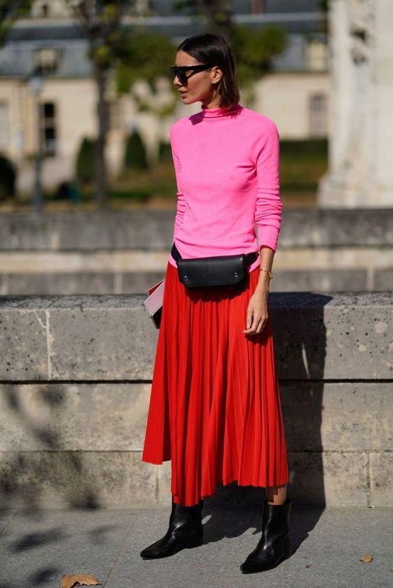Девушка в красной плиссированной юбке, розовая водолазка и черные ботильоны