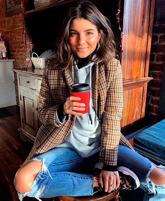 Девушка в рваных джинсах, серая худи и коричневый пиджак в клетку