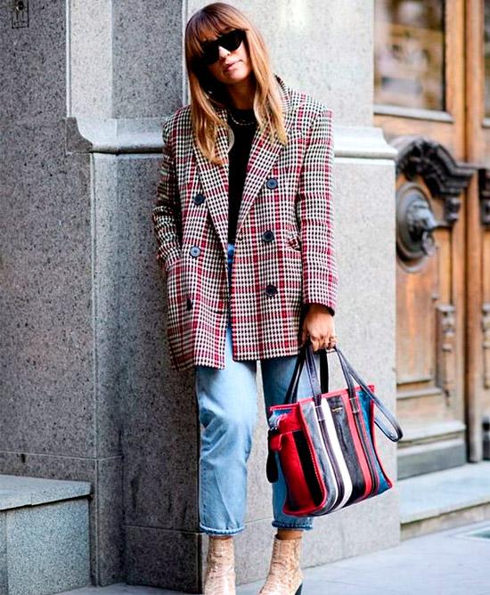 Девушка в укороченных джинсах, черная футболка и красный блейзер оверсайз в клетку, образ завершает разноцветная сумка и ботильоны