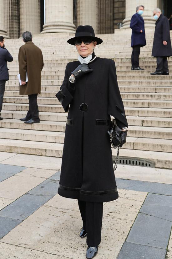 Maryse Gaspard в черном пальто и шляпе