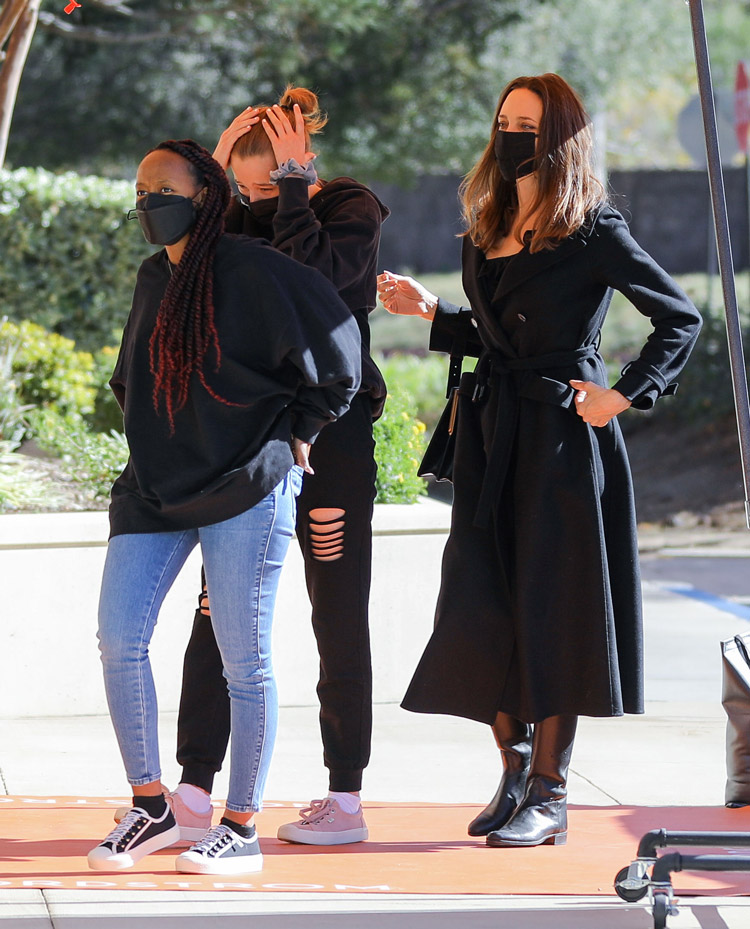 Анджелина Джоли в черных сапогах и пальто