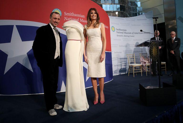 Мелания Трамп в белом платье футляр ниже колен с открытыми руками