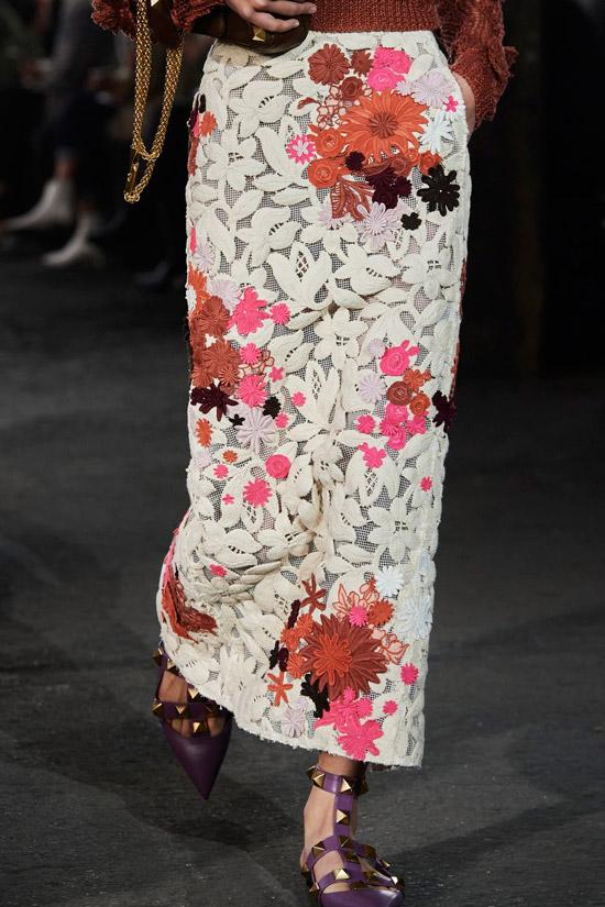 Модель в белой узкой юбке с цветочным принтом и бордовые сандалии