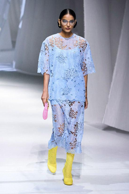 Модель в голубом костюме с прозрачными вставками, желтые сапоги