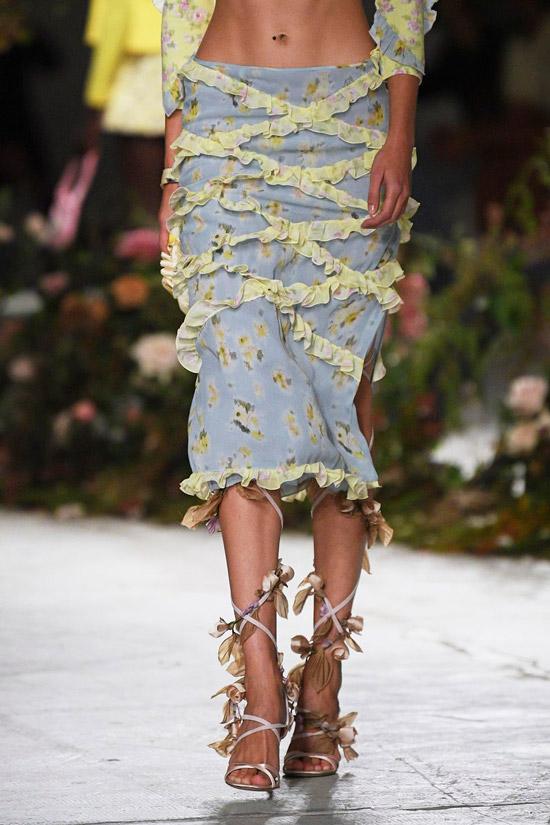 Модель в голубой юбке ниже колен с бахромой, сандалии с тонкими ремешками