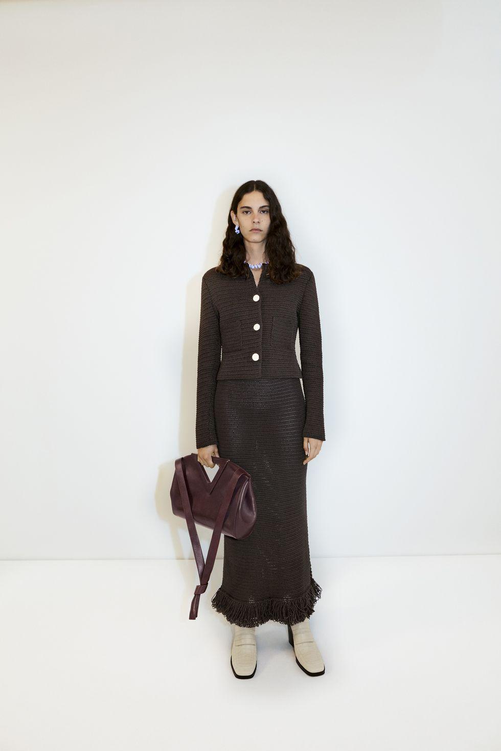 Модель в коричневом костюме с длинной юбкой, мягкая сумка и бежевые сапоги
