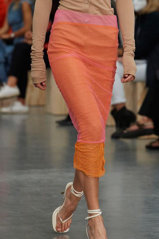 Модель в оранжевой облегающей юбке, белые босоножки на каблуке