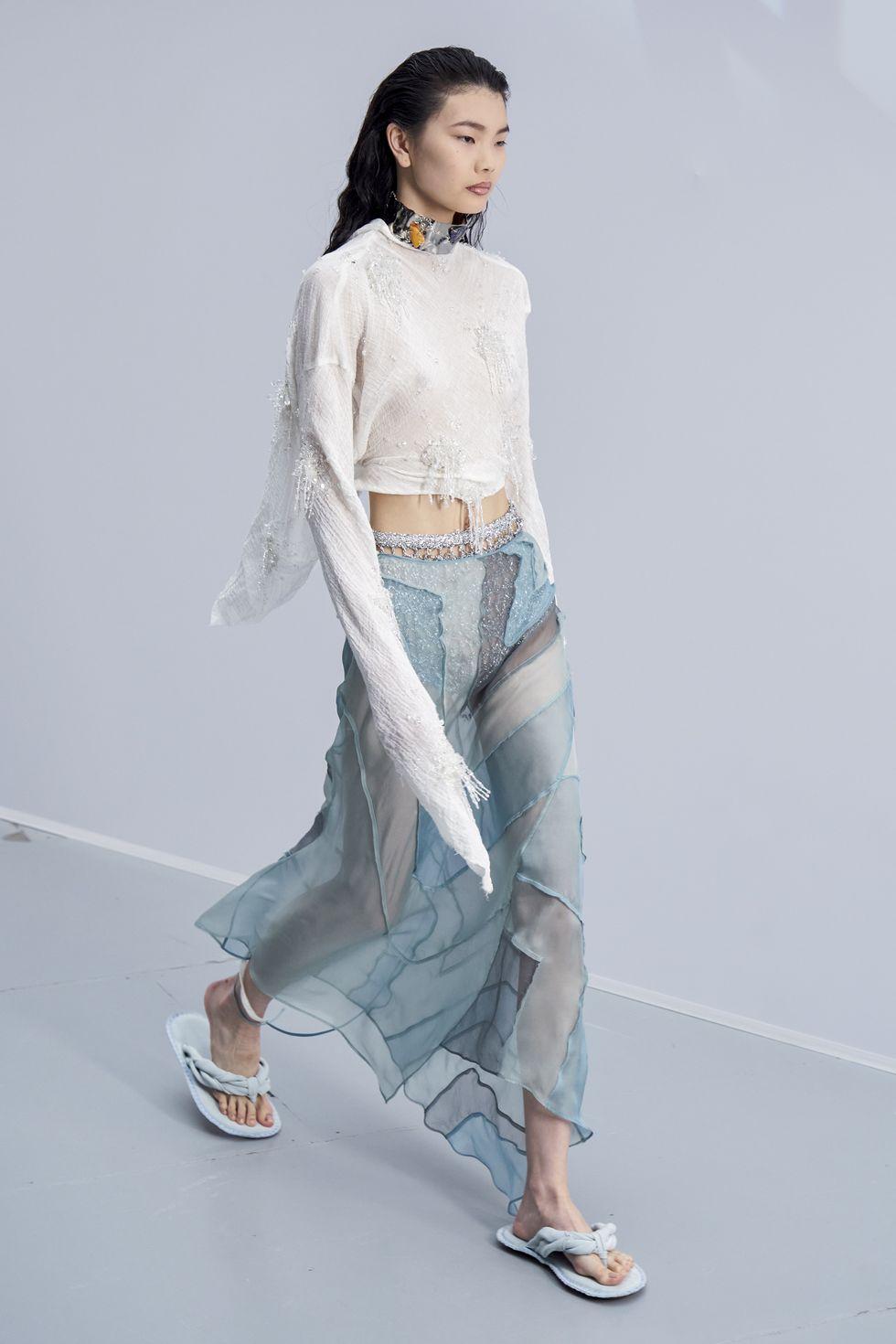 Модель в полупрозрачной юбке, белый укороченный топ и сандалии
