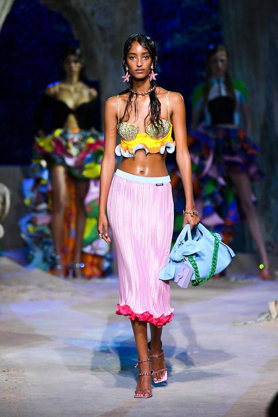 Модель в розовой юбке ниже колен и топ бюстье