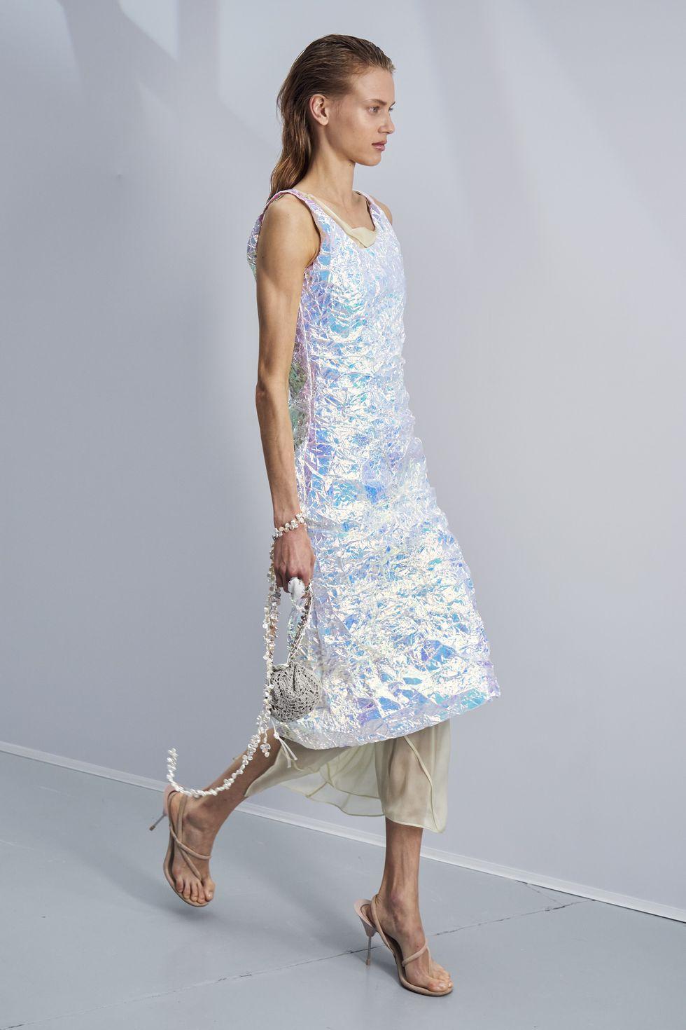 Модель в серебристом блестящем платье миди и бежевых босоножках на ремешках от Аcne