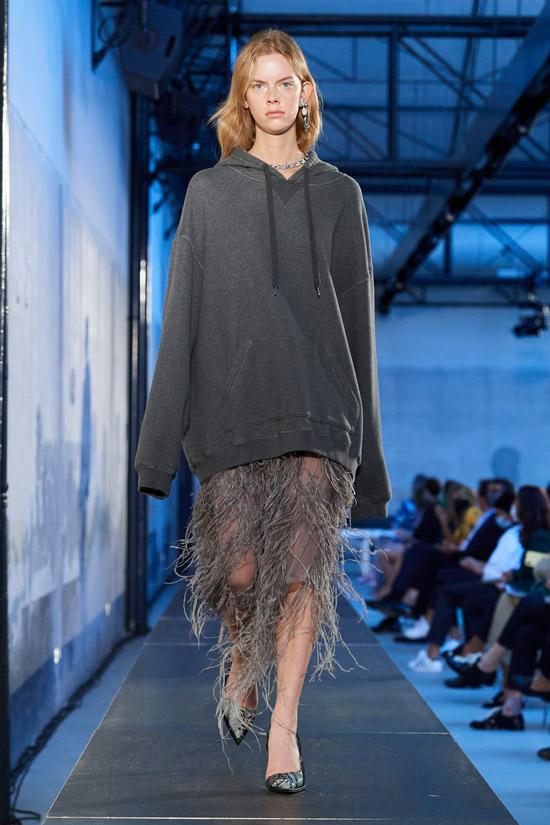 Модель в серой юбке ниже колен, толстовка оверсайз и туфли