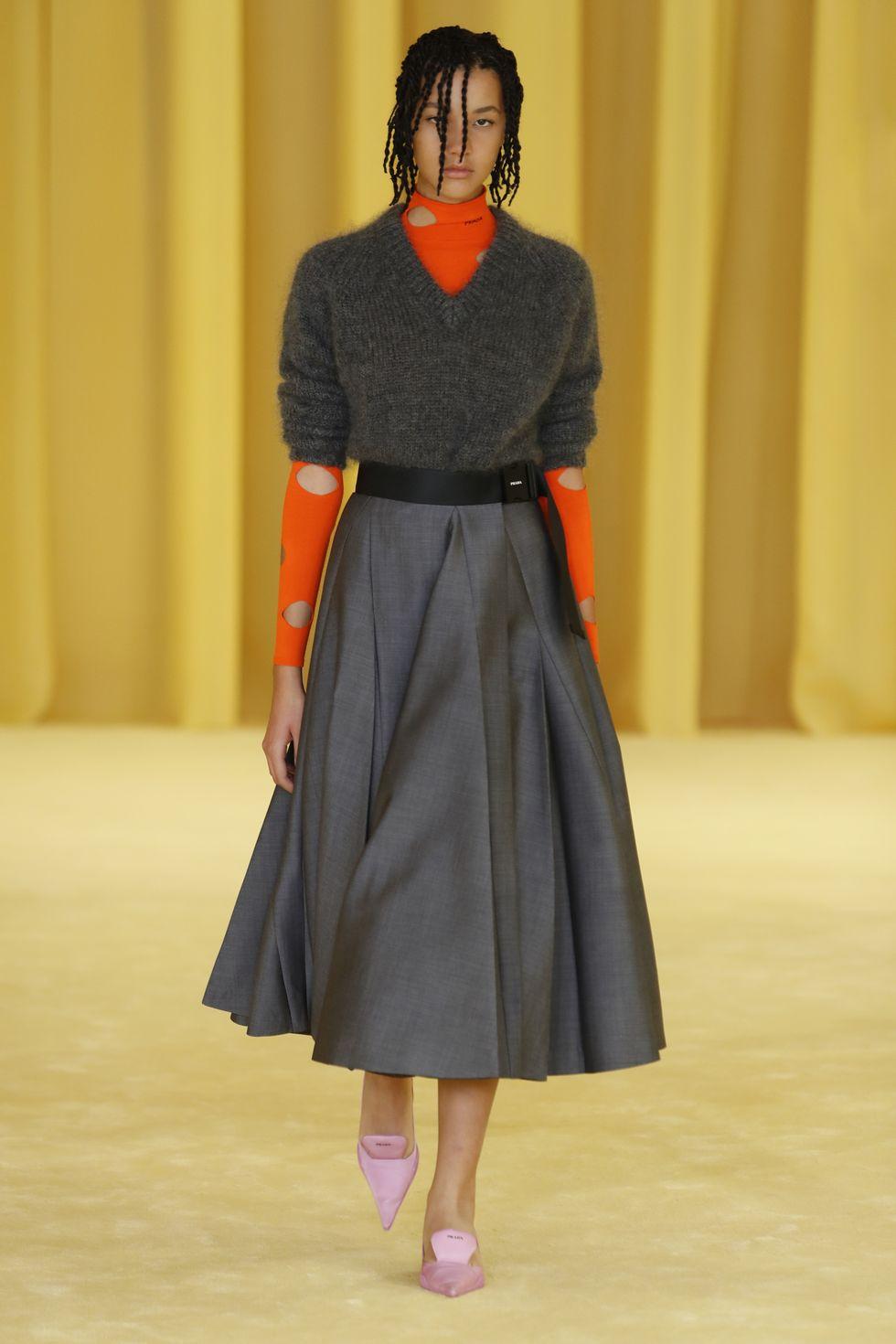 Модель в серой юбке трапеция ниже колен с поясом, оранжевая водолазка и теплая кофта