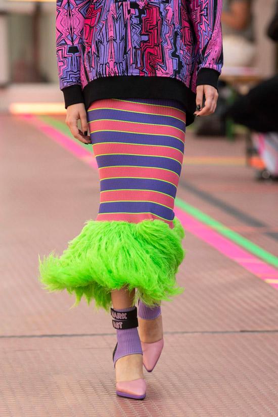 Модель в яркой юбке в полоску с зеленой бахромой и фиолетовая толстовка
