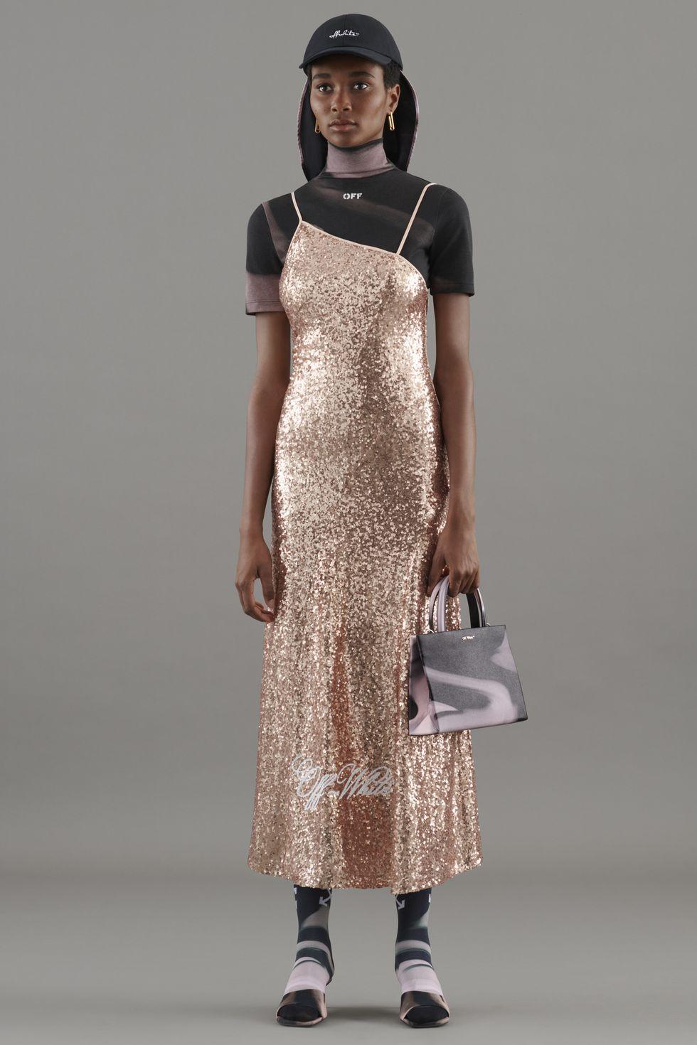 Модель в золотом платье на бретельках, черная футболка и кепка дополняют образ от Off-White