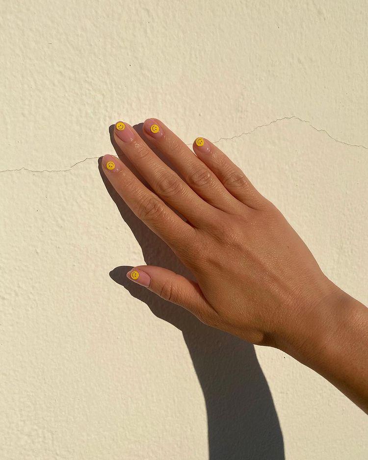 желтые веселые смайлы на нюдовых ногтях