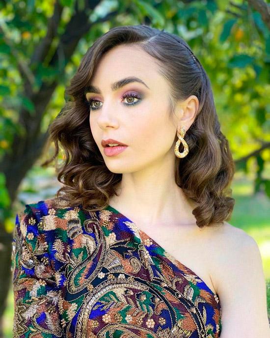 Актриса с натуральными волосами с легкими локонами с боковым пробором
