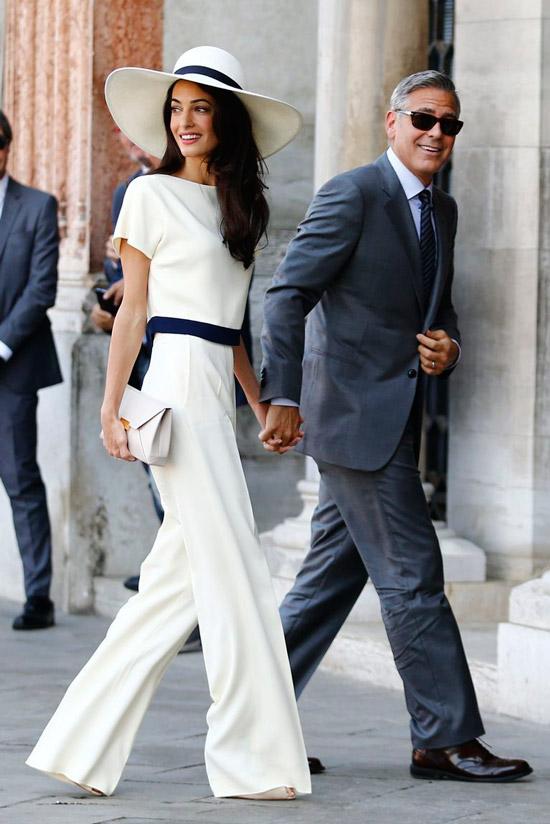 Амаль Клуни в белом костюме с широкими брюками и шляпа с черной лентой
