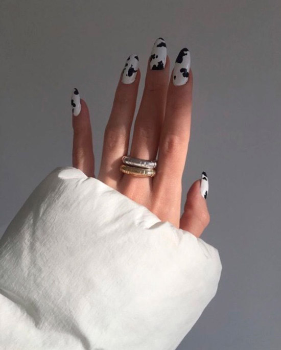 Белый маникюр с черными пятнами на длинных овальных ногтях
