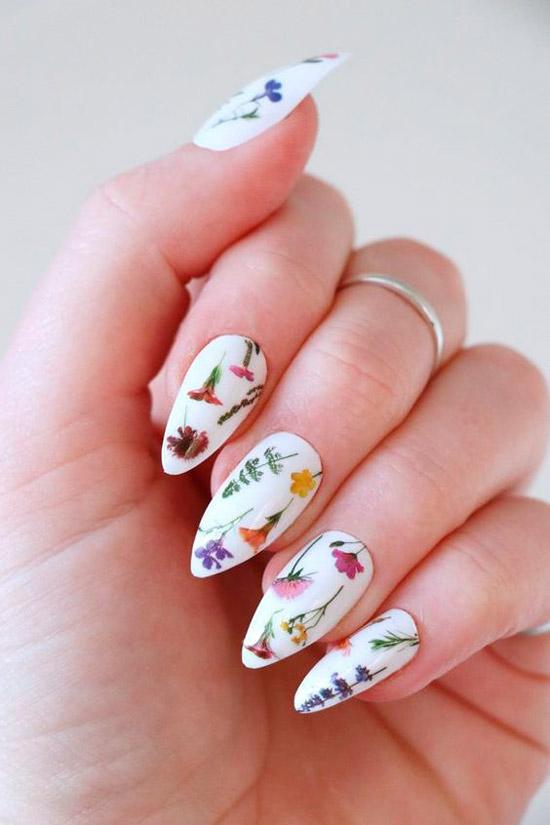 Белый маникюр с мелкими разноцветными цветами на длинных острых ногтях
